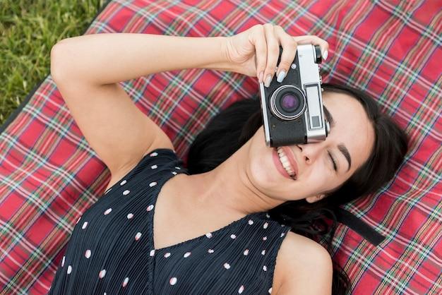 Mädchen, das ein foto auf picknickdecke macht