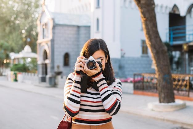 Mädchen, das ein foto mit kamera macht