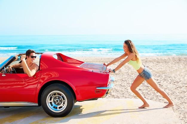 Mädchen, das ein gebrochenes auto auf dem lustigen kerl des strandes drückt
