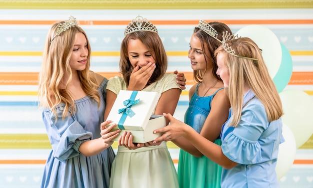 Mädchen, das ein geschenk auf einer geburtstagsfeier empfängt