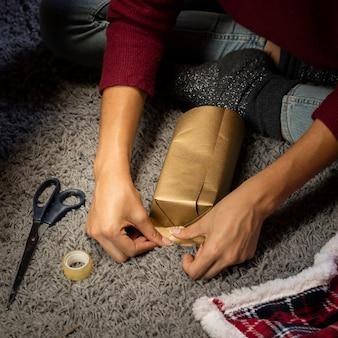 Mädchen, das ein geschenk für weihnachten bildet