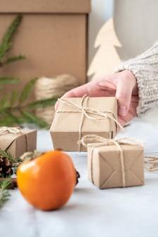 Mädchen, das ein geschenk hält, verpackt mit ihren eigenen händen, nahaufnahme. weihnachtsdekoration, design einer geschenkbox für weihnachten aus natürlichen materialien. neujahrsatmosphäre, vorbereitung auf weihnachten.
