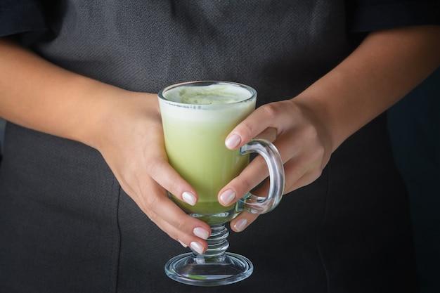 Mädchen, das ein glas mit einem matcha-grüntee-getränk hält.