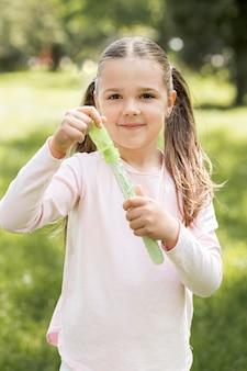 Mädchen, das ein grünes spielzeug hält