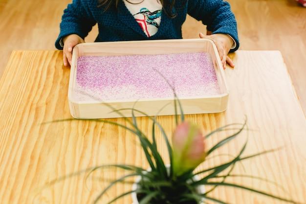 Mädchen, das ein herz auf einem tellersegment mit farbigem sand zeichnet.