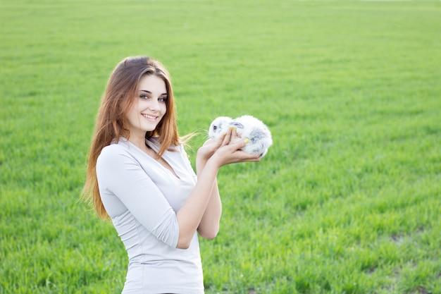 Mädchen, das ein kaninchen während auf einer grünen wiese hält.
