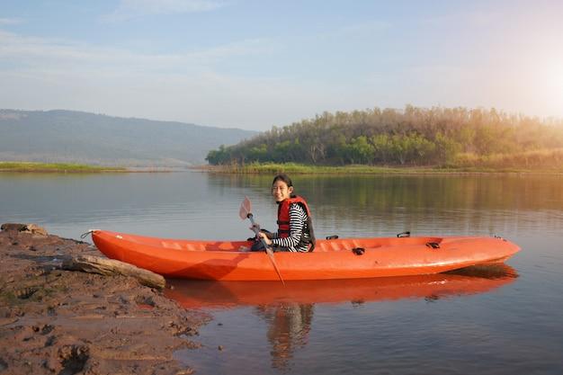 Mädchen, das ein kanu auf ruhigem wasser rudert