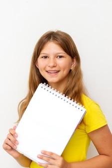 Mädchen, das ein leeres leeres notizbuch hält.