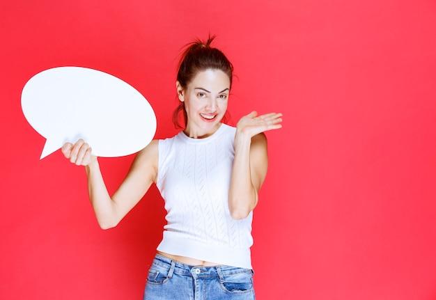 Mädchen, das ein leeres ovales ideaboard für spiele hält. Kostenlose Fotos