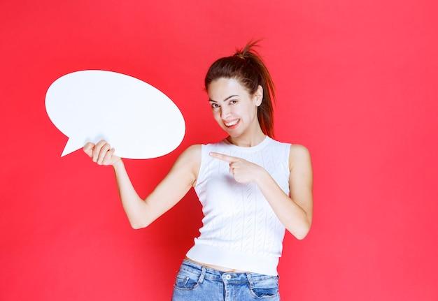 Mädchen, das ein leeres ovales ideaboard zum spielen hält und darauf zeigt.