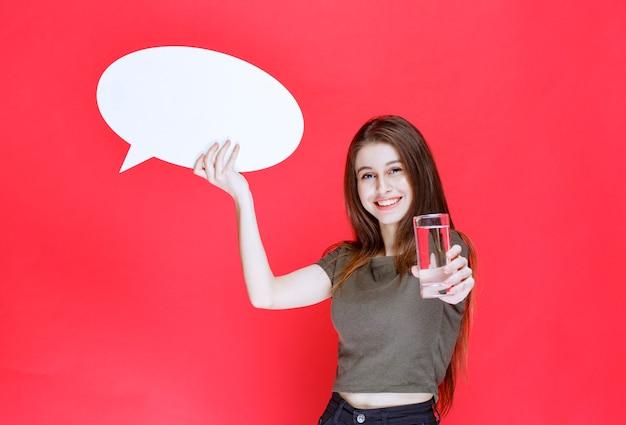 Mädchen, das ein leeres ovales thinkboard hält und ein glas reines wasser anbietet.