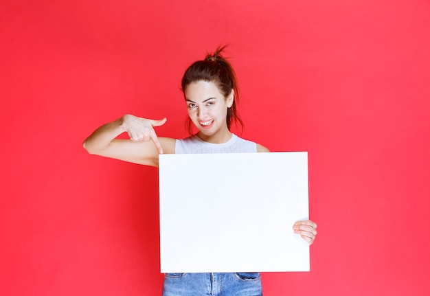 Mädchen, das ein leeres quadratisches ideaboard zum brainstorming hält.