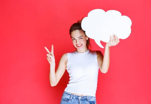 Mädchen, das ein leeres wolkenform-ideenbrett hält und es genießt.