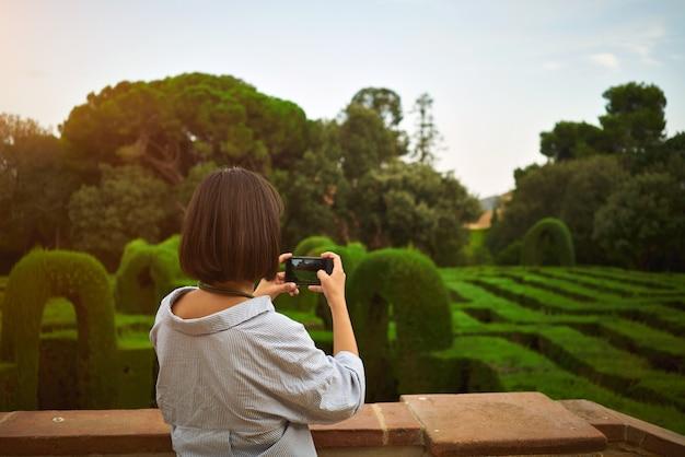 Mädchen, das ein porträt im park auf ihrem smartphone nimmt