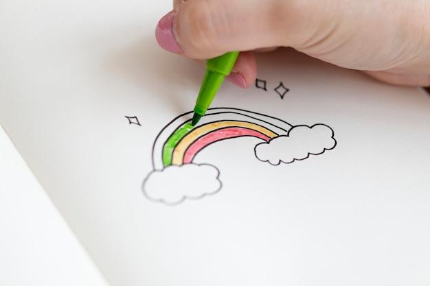 Mädchen, das ein regenbogendoodle in einem notizbuch ausmalt