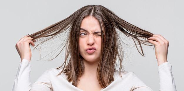 Mädchen, das ein schlechtes haar hat. tag der schlechten haare. frustrierte frau, die ein schlechtes haar hat frau mit schlechtem haar, ihr haar ist unordentlich und verheddert