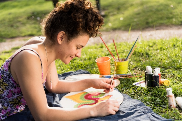 Mädchen, das ein segeltuch in einem park malt