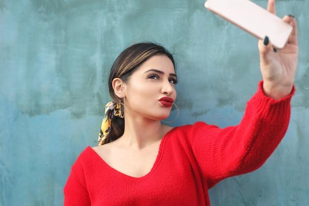 Mädchen, das ein selfie mit ihrem intelligenten telefon nimmt