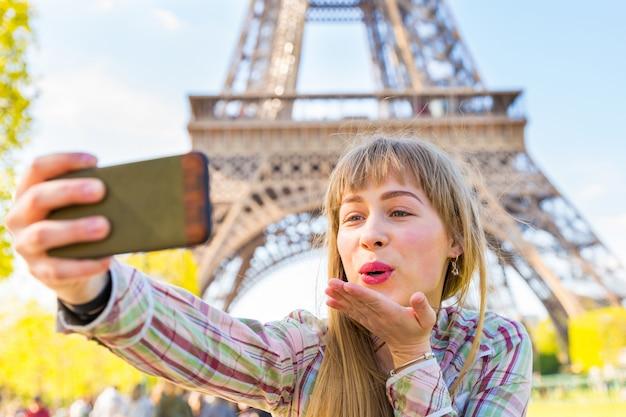 Mädchen, das ein selfie nimmt und einen kuss in paris mit eiffelturm durchbrennt