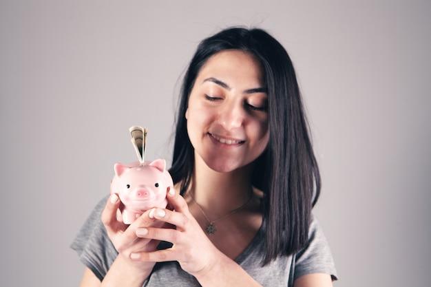 Mädchen, das ein sparschwein hält