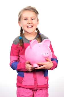 Mädchen, das ein sparschwein schüttelt