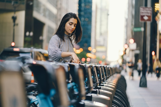 Mädchen, das ein stadtfahrrad von einem fahrradständer aus mietet