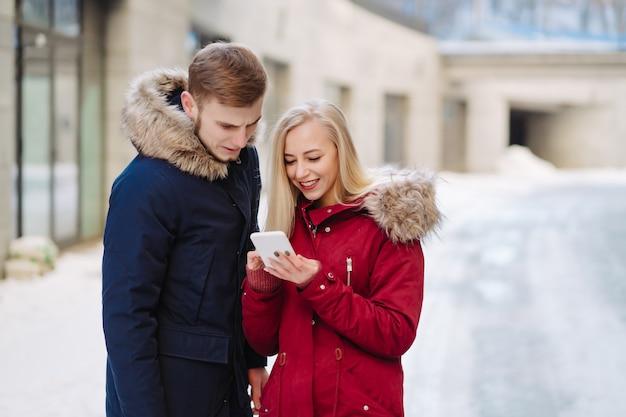 Mädchen, das ein telefon in seiner hand und in ihnen betrachten den smartphone hält.