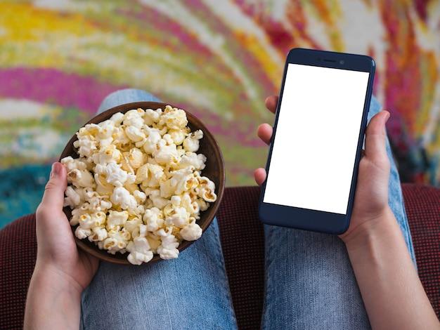Mädchen, das ein telefon mit abschneidender weißer oberfläche hält. eine schüssel popcorn auf dem schoß des kindes.