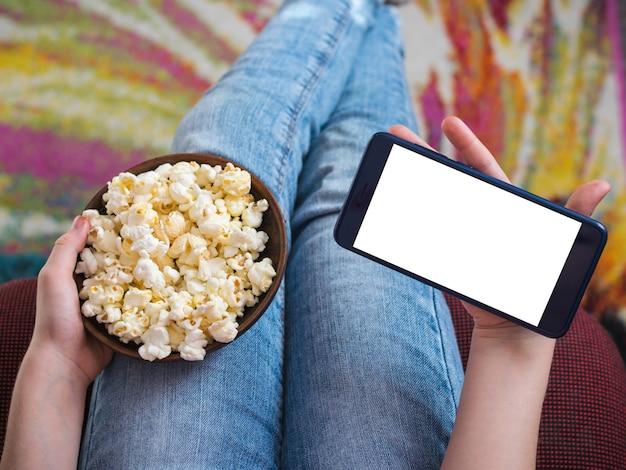 Mädchen, das ein telefon mit schnittfläche hält. eine schüssel popcorn auf dem schoß des kindes.