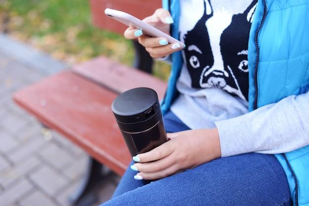 Mädchen, das ein telefon und eine schale heißen cappuccinokaffee hält