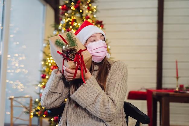 Mädchen, das ein weihnachtsgeschenk am silvesterabend hält. mädchen, das in die kamera schaut. weihnachten während coronavirus, konzept