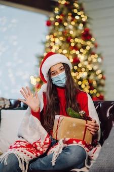 Mädchen, das ein weihnachtsgeschenk am silvesterabend hält.