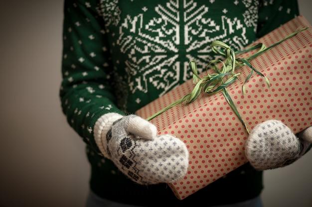 Mädchen, das ein weihnachtsgeschenk anhält.