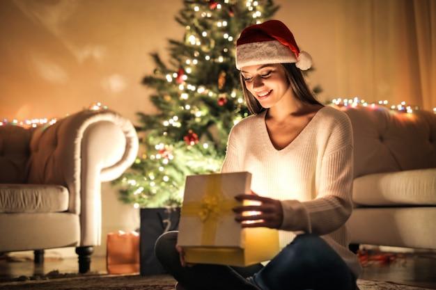 Mädchen, das ein weihnachtsgeschenk auspackt