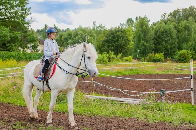 Mädchen, das ein weißes pferd auf natur reitet