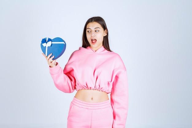 Mädchen, das eine blaue geschenkbox hält und es betrachtet
