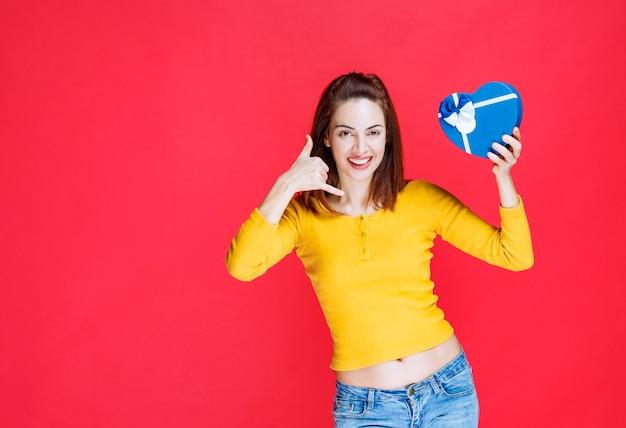 Mädchen, das eine blaue geschenkbox in herzform hält und um einen anruf bittet