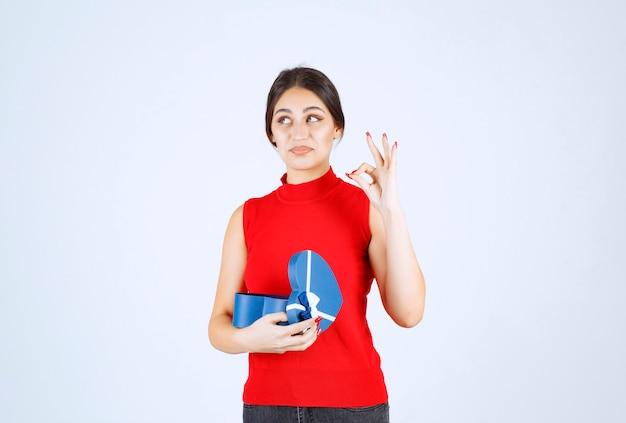 Mädchen, das eine blaue geschenkbox öffnet und das geschenk genießt.