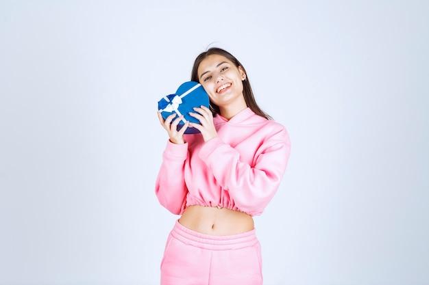 Mädchen, das eine blaue herzform-geschenkbox hält und es demonstriert