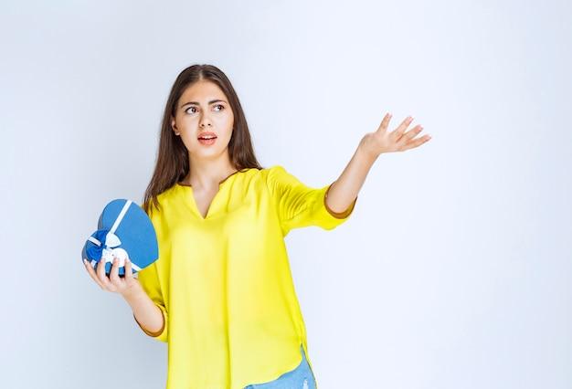 Mädchen, das eine blaue herzform-geschenkbox hält und überrascht und erschrocken aussieht.