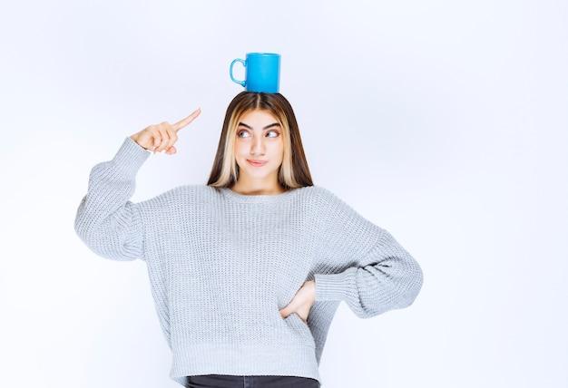Mädchen, das eine blaue kaffeetasse an ihrem kopf hält.