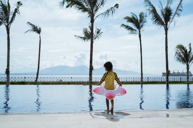 Mädchen, das eine boje ein kind trägt, steht am pool