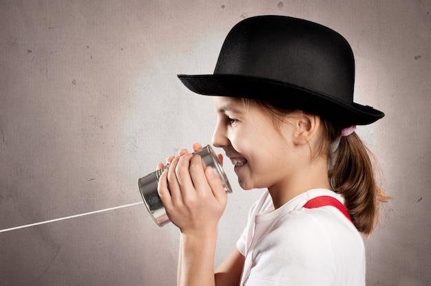 Mädchen, das eine dose als telefon verwendet