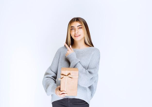 Mädchen, das eine geschenkbox aus karton hält und einen empfänger beiseite zeigt.