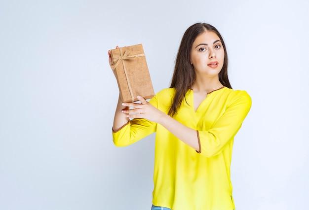 Mädchen, das eine geschenkbox aus karton hält und sich positiv fühlt.