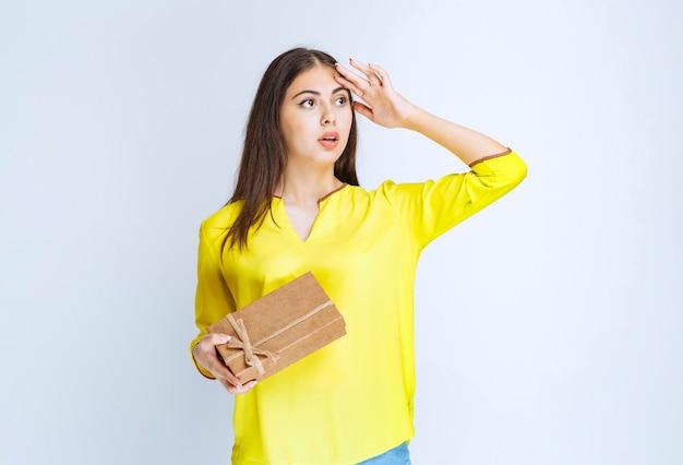 Mädchen, das eine geschenkbox aus karton hält und verwirrt oder nachdenklich aussieht.