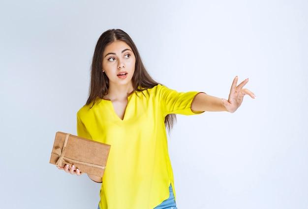 Mädchen, das eine geschenkbox aus karton und eine sehnsüchtige hand hält, um eine andere zu nehmen.