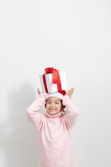 Mädchen, das eine geschenkbox in der strickjacke und in sankt-hut hält