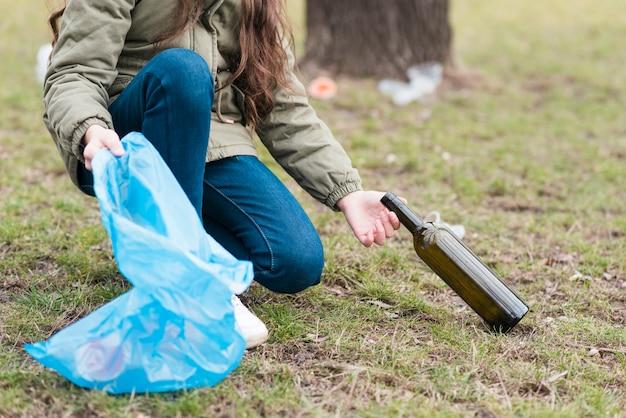 Mädchen, das eine glasflasche vom boden reinigt