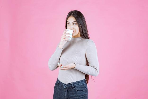 Mädchen, das eine kaffeetasse hält und es trinkt